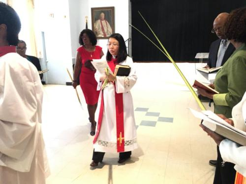 Reverend Ajung Sojwal and parishioners in Palm Sunday processional from Regan Hall